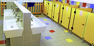 Badkamers van een kinderdagverblijf met witte gootstenen en gele toiletdeuren stock afbeelding
