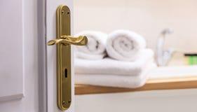 Badkamers van open deur Rolden de onduidelijk beeld witte handdoeken en vouwden naast de gootsteen Details van de deur Royalty-vrije Stock Foto