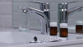 Badkamersbeeld met vele pillen en drugs verlaten op de gootsteen stock videobeelden