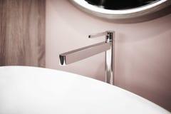 Badkamersbinnenland in warme beige tonen met gootsteen, spiegel en tapkraan Stock Afbeelding