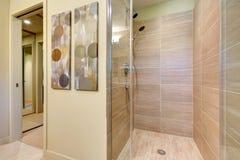 Badkamersdouche met glasdeuren en natuurlijke kleurentegels. Stock Afbeeldingen