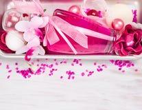 Badkosmetik stellte mit rosa Parfümflasche, Aromasalz, Band und Badblumen ein Lizenzfreie Stockfotos