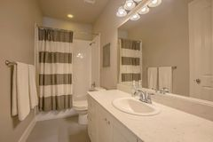 Badkuip en douche met een gestreept gordijn binnen een kleine badkamers stock foto