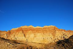 Badland Sunset. Golden light of sunset against badland hills with blue sky Stock Photography