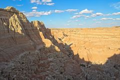 Badlands National Park Canyon in Shadow. Badlands National Park Canyon in South Dakota with shadows, blue sky and clouds stock image
