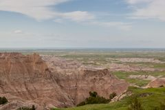 Badlands National Park Mountain Formations. Dramatic mountain formations carved out by erosion showing layers of rocks with spring grass and distant flat prairie royalty free stock photography