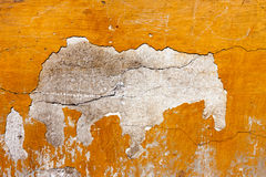 Badly damaged red plaster wall background Stock Image