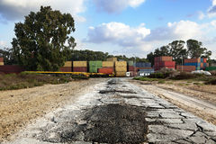 Road to Cargo Containers Storage. A badly patched broken asphalt road leads to a storage yard of cargo containers used for freight Stock Images