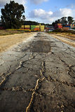 Road to Cargo Containers Storage. A badly patched broken asphalt road leads to a storage yard of cargo containers used for freight Royalty Free Stock Photography