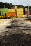 Road to Cargo Containers Storage. A badly patched broken asphalt road leads to a storage yard of cargo containers used for freight Stock Photo