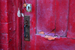 Badly peeling paint on door. Badly peeling paint on door with old rusting fittings Royalty Free Stock Photos
