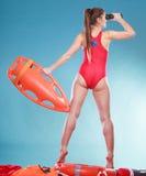 Badmeester op plicht met reddingsboei het controleren Stock Foto's