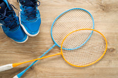 Badminton accessories. Shoes and a rocket on a wooden floor Royalty Free Stock Images