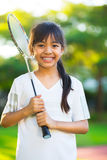 Badminton. Closeup cute little asian girl holding a badminton racket Royalty Free Stock Photo
