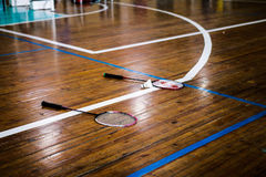 Two badminton rackets and shuttlecocks. Lie on the floor of a sports hall Stock Images