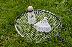 Badminton equipment on grass. Badminton equipment including rackets and two shuttlecocks on grass background stock photos