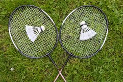 Badminton equipment on grass. Badminton equipment including rackets and two shuttlecocks on grass background royalty free stock image