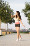 A badminton playing girl. An asian girl is playing badminton very happily in garden Stock Images