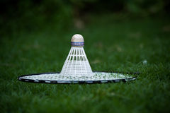 Badminton racket and shuttlecock. Badminton racket and shuttlecok shot outdoors against the background of green grass in a lawn Stock Image