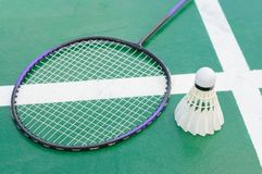 Badminton racket and shuttlecocks on court.. Badminton racket and shuttlecocks on green court Stock Photo