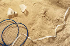 Badminton rackets, net and shuttlecock on the sand, top view. Summer background Royalty Free Stock Photos