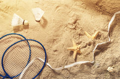 Badminton rackets, net, shuttlecock and starfish on the sand. Top view. Summer background Stock Photo