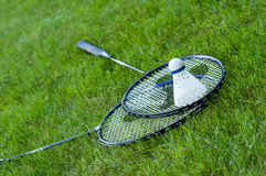Badminton rackets. And shuttlecock lying on green grass Stock Images