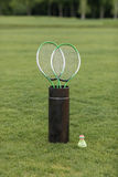 Badminton racquets in container and shuttlecock on green grass Stock Photos