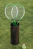 Badminton racquets in container and shuttlecock on green grass Royalty Free Stock Photos