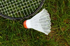 Badminton shuttlecock. And racket on green grass; in horizontal orientation Stock Image