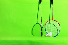Badminton racket and shuttlecock feathers on light green background with text space. Badminton shuttlecock and racket lie on the green background with copy Royalty Free Stock Images