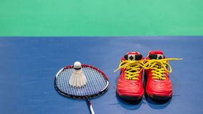 Badminton shuttlecock on racket and red shoe on badminton court.  Royalty Free Stock Image