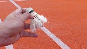 Badminton-Spieler, der einen Federball servierfertig hält stock video