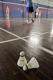 Badminton-two shuttlecocks in the badminton courts. Badminton - two shuttlecocks in the badminton courts with players competing Stock Image