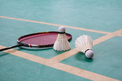 Badminton. White badminton shuttlecock on a green floor with blurred players in badminton court Royalty Free Stock Photography
