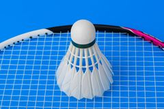 Badmintonfjäderboll och racket på blå bakgrund Arkivfoto