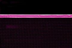 Badmintonrosa färger som är netto inomhus på badmintondomstolen, closeupsikt av badminton som är netto med svart bakgrund arkivfoto