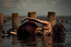 Badning för ung kvinna i terapeutiskt vatten av gyttjabreda flodmynningen arkivfoto