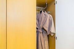 Badrockar som hänger i garderoben, brun badrock med trähängaren Arkivfoto