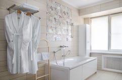 Badrum i varma färger, med en toalett, ett badkar, en hårtork, en spegel, en tork för kläder Royaltyfri Bild