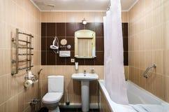 Badrum i varma färger, med en toalett, ett badkar, en hårtork, en spegel, en tork för kläder Arkivbilder