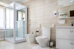 Badrum i varma färger, med en toalett, ett badkar, en hårtork, en spegel, en tork för kläder Arkivbild