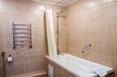 Badrum i varma färger, med en toalett, ett badkar, en hårtork, en spegel, en tork för kläder Royaltyfri Fotografi