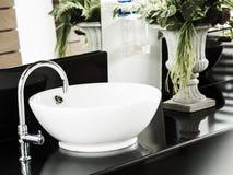 Badrum med den vita vasken och vattenkranen royaltyfri foto