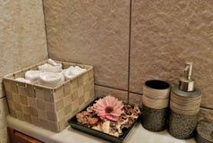 Badrum med handdukar, blommor och omsorgkrämer arkivbilder