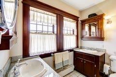 Badrum med kabinetter för mörk brunt och det stora fönstret Royaltyfria Bilder