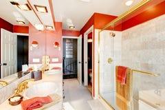 Badrum med röda väggar och den walk-in duschen. Fotografering för Bildbyråer