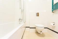 Badrum med toaletten och badkaret Arkivfoto