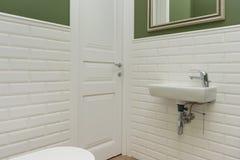 Badrum närbild för toalettruminre Väggarna är målad gräsplan som är dold med dekorativa keramiska tegelplattor med vitt glansigt  arkivfoton