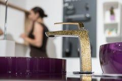 Badrumdetalj i nytt lyxhem: vask och guld- vattenkran med partisk sikt av den near spegeln för kvinna royaltyfria foton